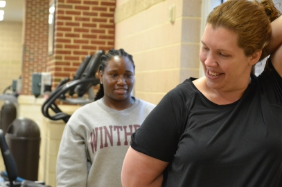 Ryan Earle, a student trainer at Winthrop University, watches her client Kat West perform a stretch (photo: La J'ai Reed).