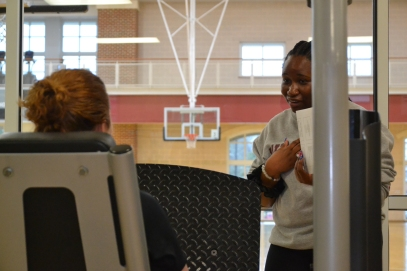 Ryan Earle, a Winthrop student trainer preps her client, Winthrop professor Kat West, to complete workouts on one of the West Center's leg press machines (photo: La J'ai Reed).