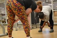 To close out the work out, professor Kat West, and Ryan Earle, a student trainer, stretch various parts of their bodies (photo: La J'ai Reed).