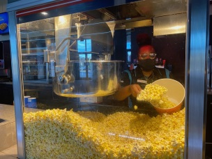 Nakia Williams, an employee at the Regal Manchester movie theater in Rock Hill, S.C., prepares popcorn for a customer. Popcorn, candy and drinks are the only concession snacks they are serving customers due to the COVID-19 pandemic (photo: Jendaya Fleming).