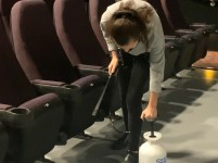 Tatyana Peshkov, a manager at Regal Manchester, sprays disinfectant on all of the movie theater seats. Employees and managers now do this after customers have left the theater, due to new company guidelines as a result of the COVID-19 pandemic (photo: Jendaya Fleming).