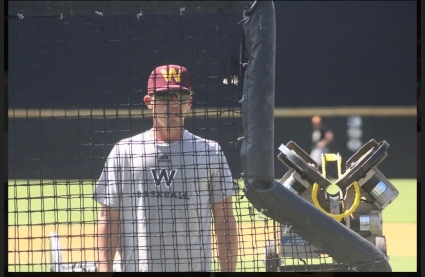 Winthrop assistant baseball coach Chris Clare protects himself behind the screen while feeding the hitting machine during batting practice Aug. 28 at the Winthrop Ballpark (photo: Joey Tepper).